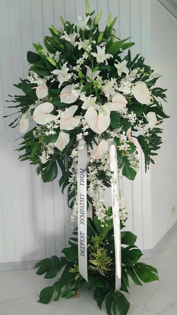all white standing arrangement with lilies, anthuriums, and orchids