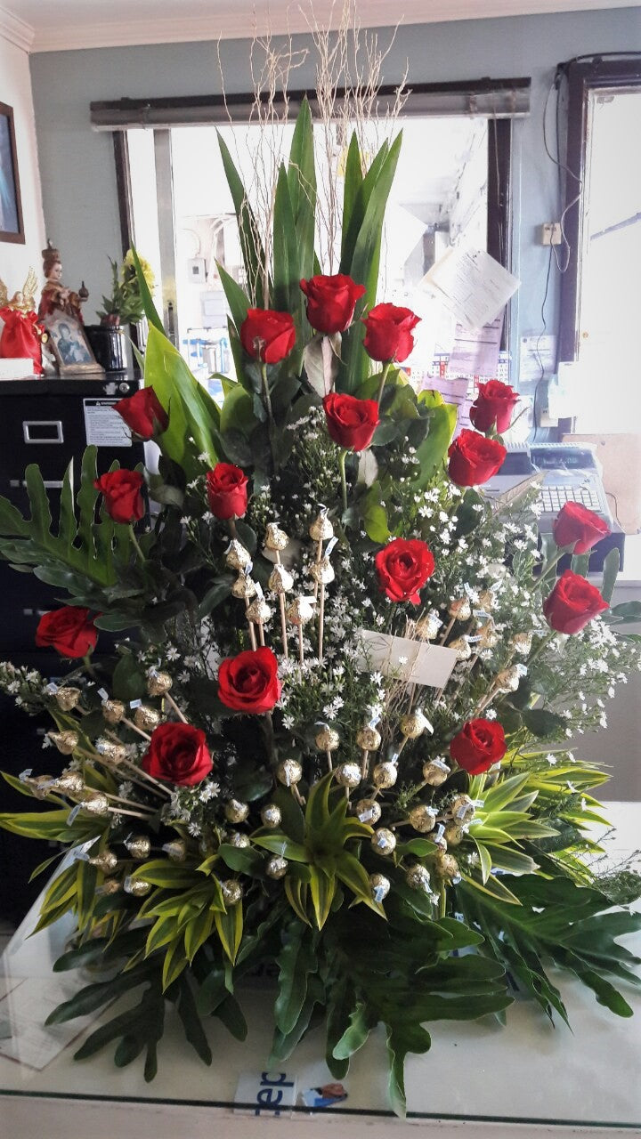 Half faced arrangement with red roses and chocolates on sticks