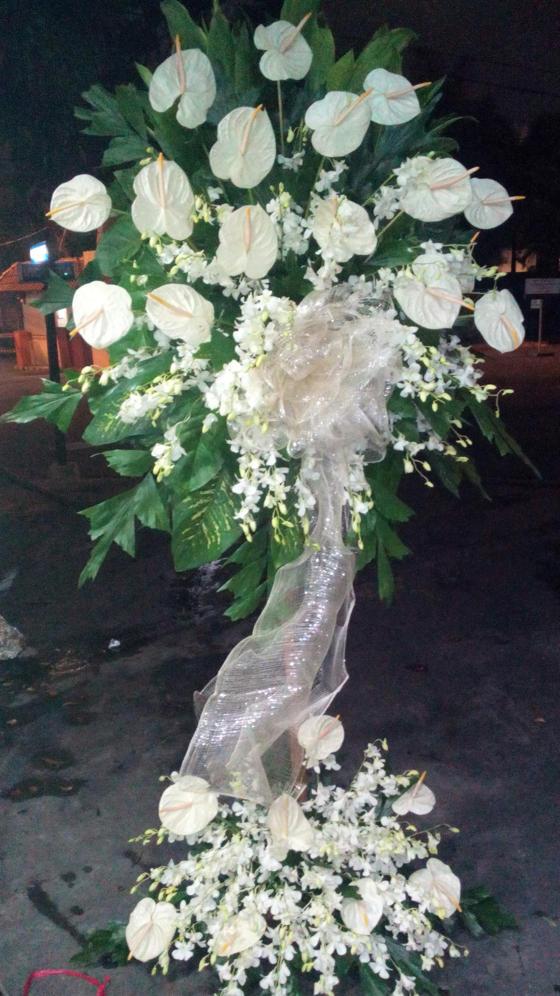 all white standing arrangement with anthuriums and orchids