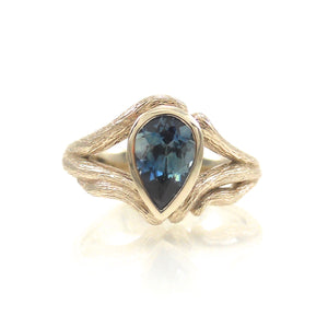 organic handcrafted engagement ring featuring a bezel set center stone in a vine and leaf inspired setting