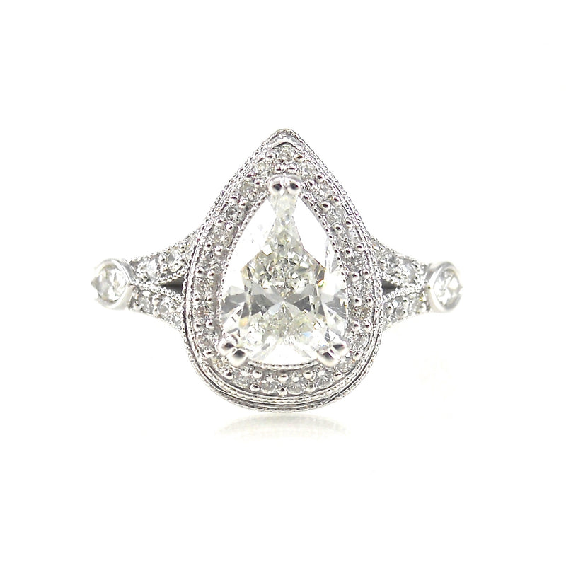 halo engagement ring featuring a pear shaped center stone with round brilliant diamond and milgrain accents