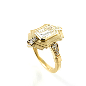 art deco inspired design with a bezel set center stone and diamond accents