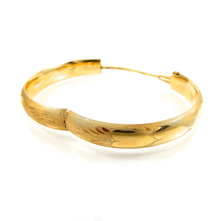 14k yellow-gold hinged bangle featuring a decorative finish with a heart motif