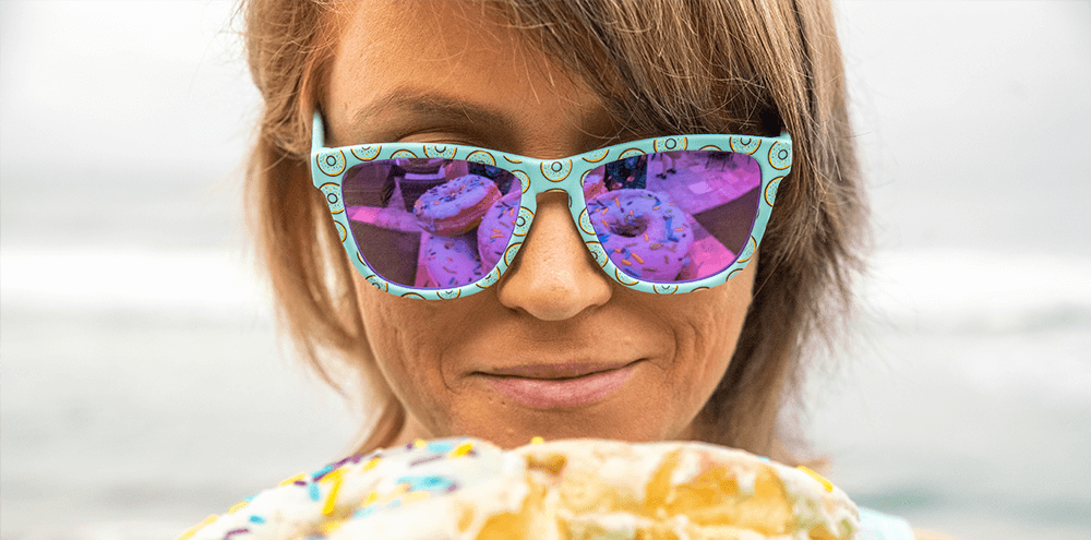 Woman wearing Goodr Glazed and Sunglasses eating sugary donut