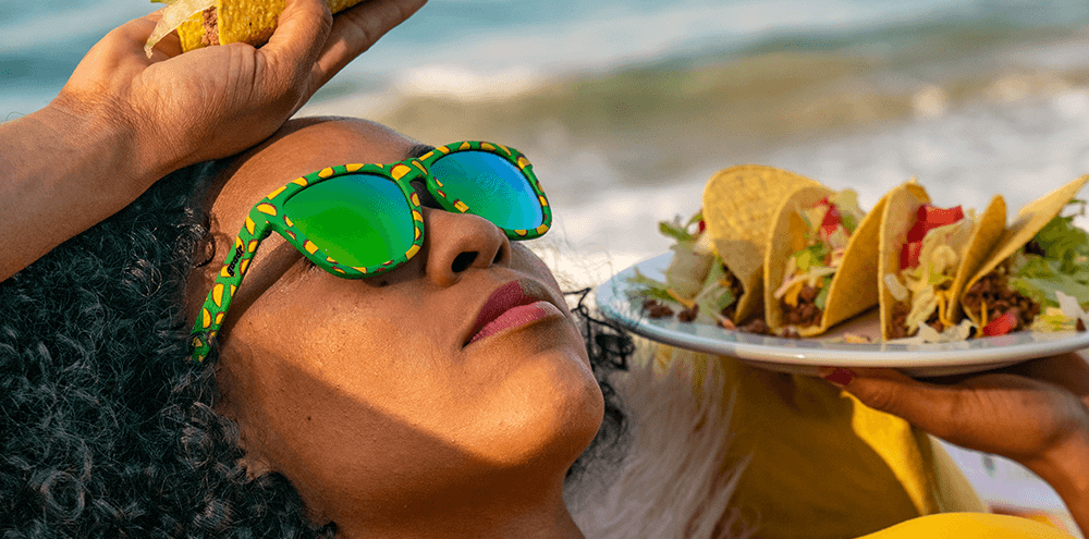 Woman wearing Goodr Hope They Serve Tacos in Hell Sunglasses eating a Taco.