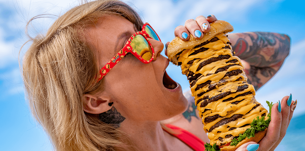 Woman wearing Goodr Sun's Out, Buns Out Sunglasses eating a massive Hamburger