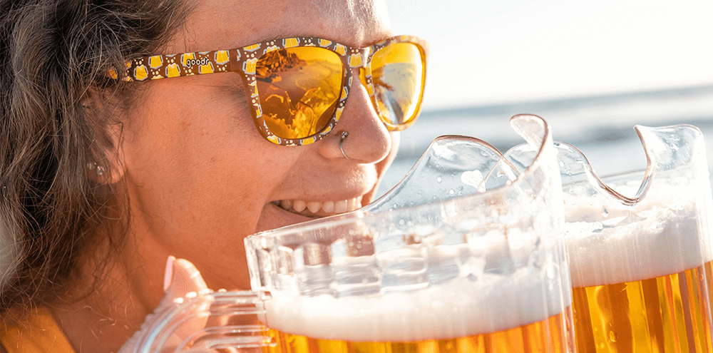 Woman wearing Goodr Take a Pitcher, It'll Last Sunglasses drinking from beer pitcher on beach