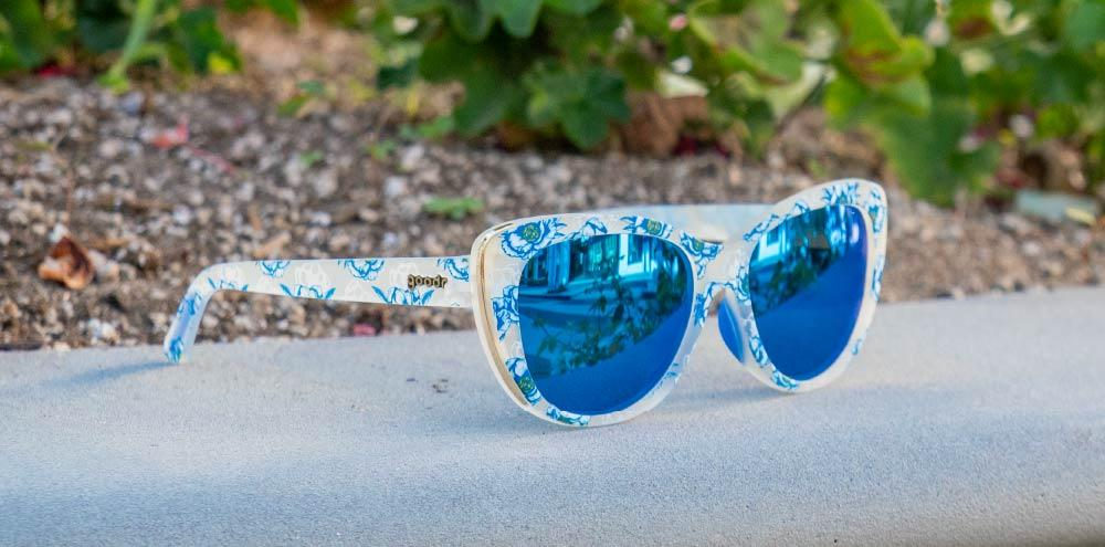 Blue Floral Cateye goodr - Runways - Sitting on urban wall