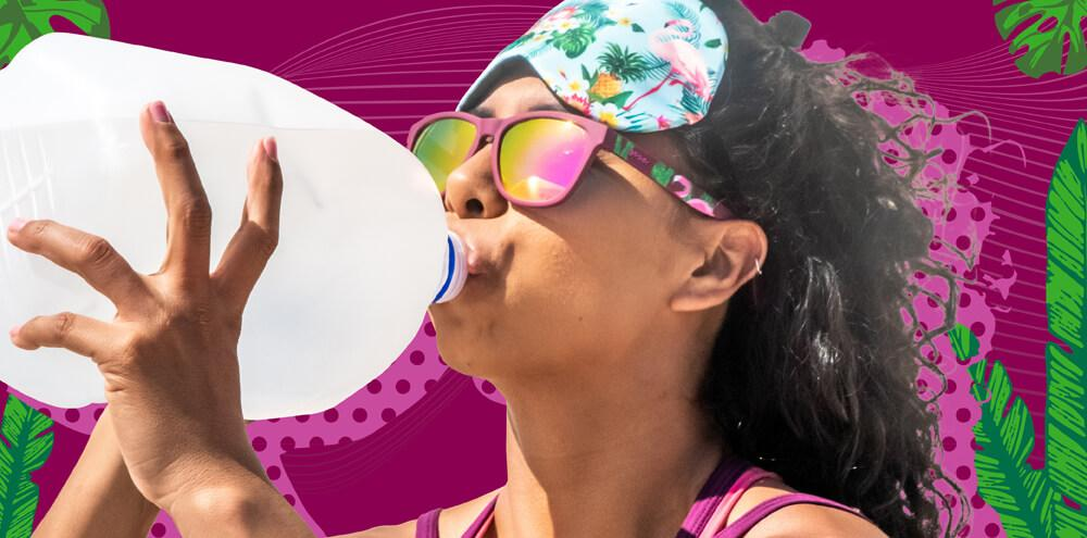 Woman wearing Goodr Hungover in the Oasis Sunglasses drinking from a large water bottle