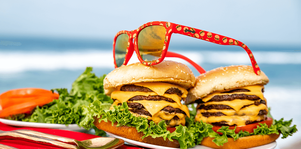 Goodr Sun's Out, Buns Out Sunglasses resting on Hamburgers
