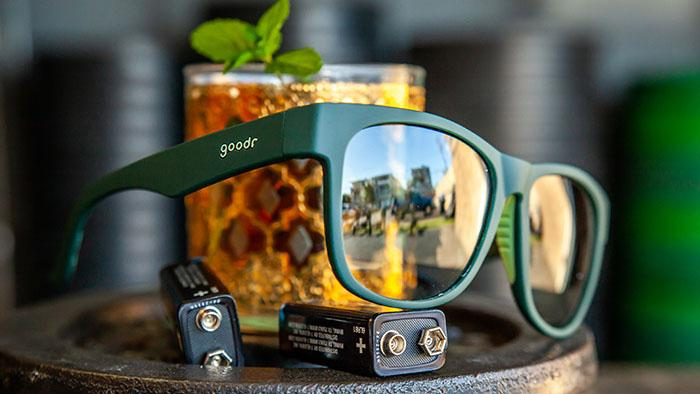 Goodr Sunglasses with a Green Frame Sitting Next To a Cocktail