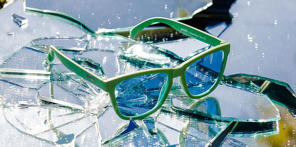 Goodr Green and Blue Running Sunglasses sitting on a glass table