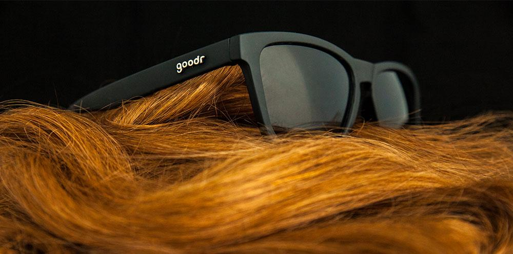 Goodr Black Framed Running Sunglasses Sitting On Red Hair