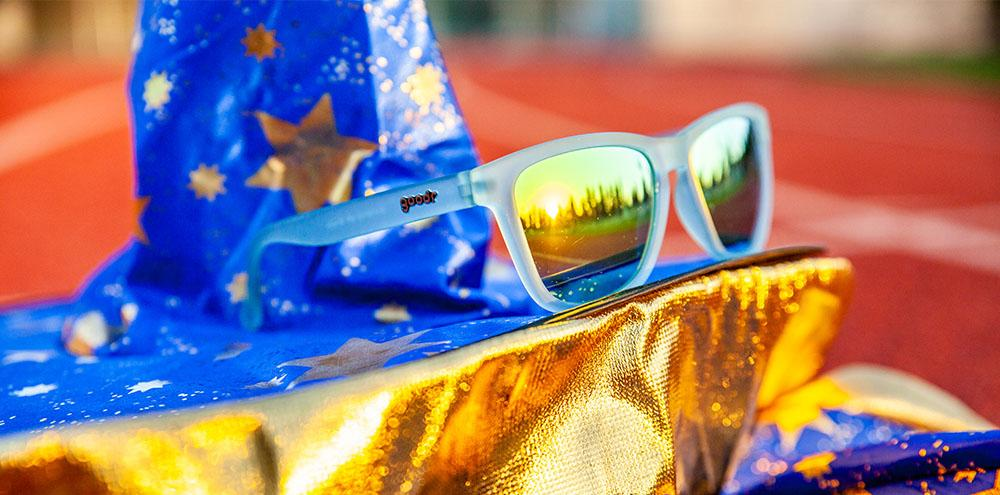 Goodr Light Blue and Gold Running Sunglasses Sitting On A Wizards Hat