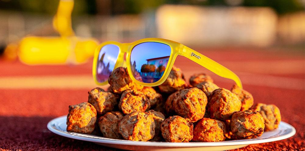 Goodr Sunglasses – Swedish Meatball Hangover sitting on a plate of meatballs