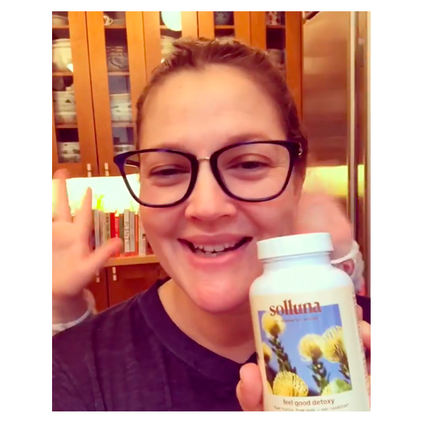 Drew Barrymore holds up a bottle of Solluna's Feel Good Detoxy 2.0