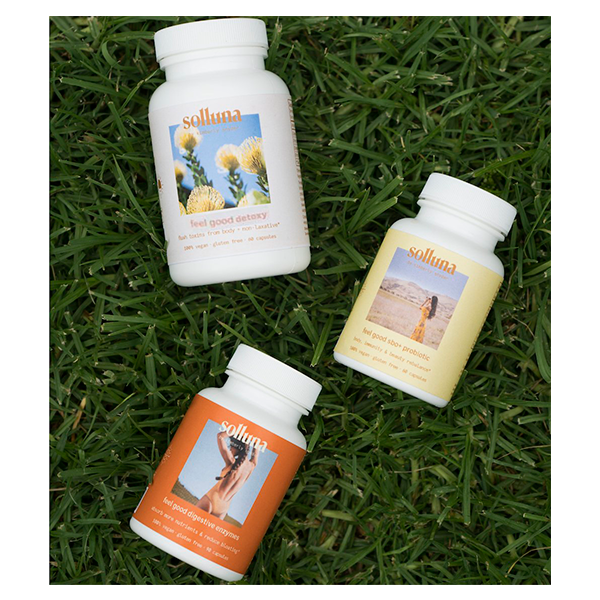 Feel Good Starter Kit bottles include Detoxy 2.0, Digestive Enzymes and SBO Probiotics laying in the grass