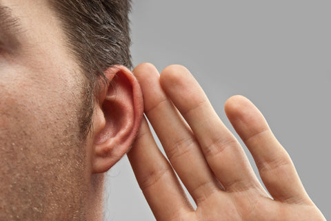 man with hand behind his ear