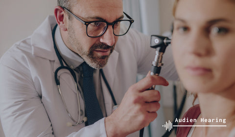 doctor looking at patients ear with otoscope