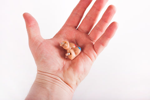 A pair of completely in canal (CIC) hearing aids in the palm of a hand