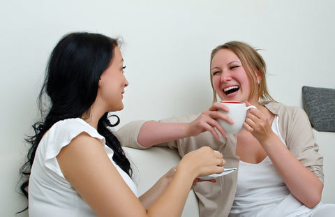 Two women friends chatting over coffee at home