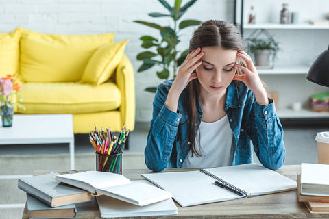 Concentrated girl with headache sitting at desk and studying at home