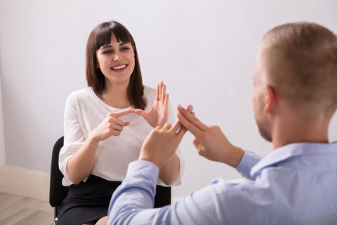 Smiling Young Woman And Man Talking With Sign Language