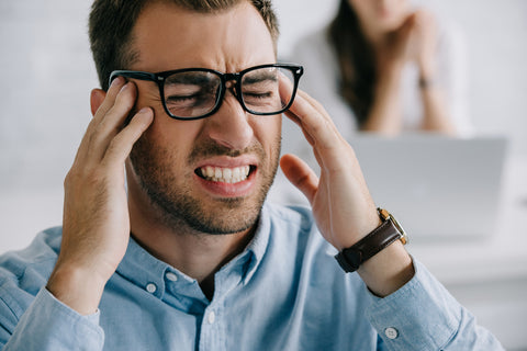 Close-up view of young businessman in eyeglasses suffering from headache in office
