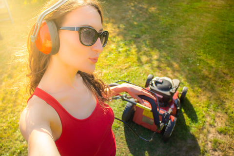 Young beautiful woman making selfie while mows the lawn