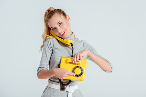 Woman dialing phone number on vintage yellow telephone isolated on grey