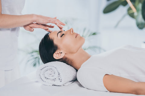 reiki specialist doing healing therapy to calm young woman
