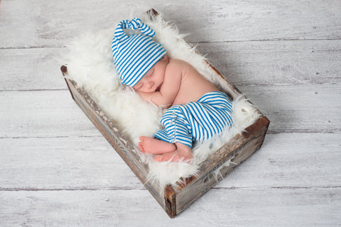 Newborn baby wearing blue and white striped pajamas and sleeping in a vintage, wooden, soda pop crate