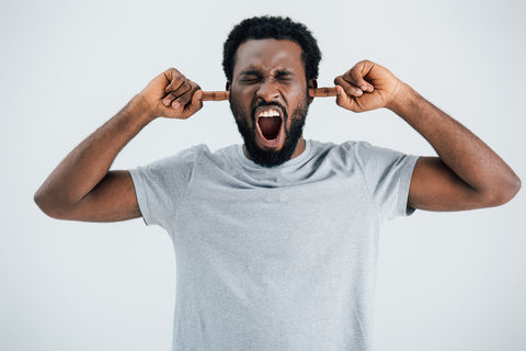 Emotional african american man in grey t-shirt shouting and closing ears isolated on grey
