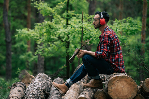 Thoughtful lumberman holding ax while sitting on logs in forest and looking away