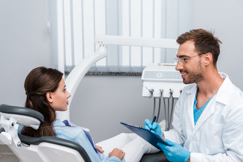 Handsome doctor in glasses holding pen and clipboard near attractive patient