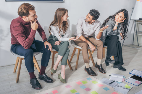 Happy multicultural coworkers sitting on chairs in office