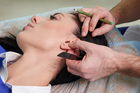 Plastic surgeon examines ear of patient before plastic surgery