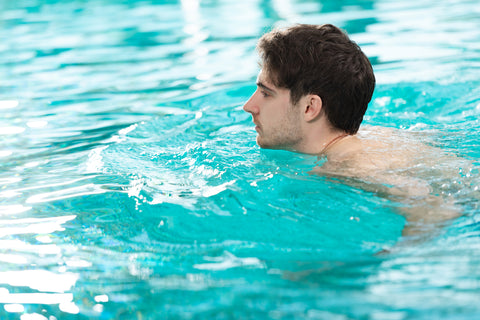 young man swimming in swimming pool