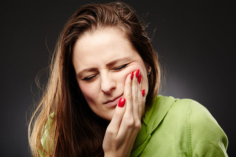 Young woman having a severe tooth ache with hand on cheek