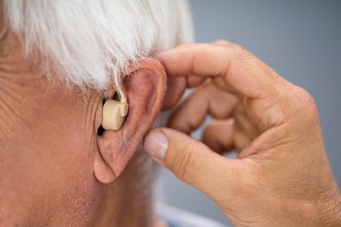 old man putting hearing aid in the ear