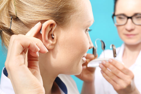 An image showing a lady fitting a hearing aid with the help of an audiologist