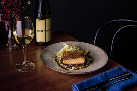 Bottle of Riesling stands next to half full glass, alongside pan seared salmon and fennel on ceramic plate