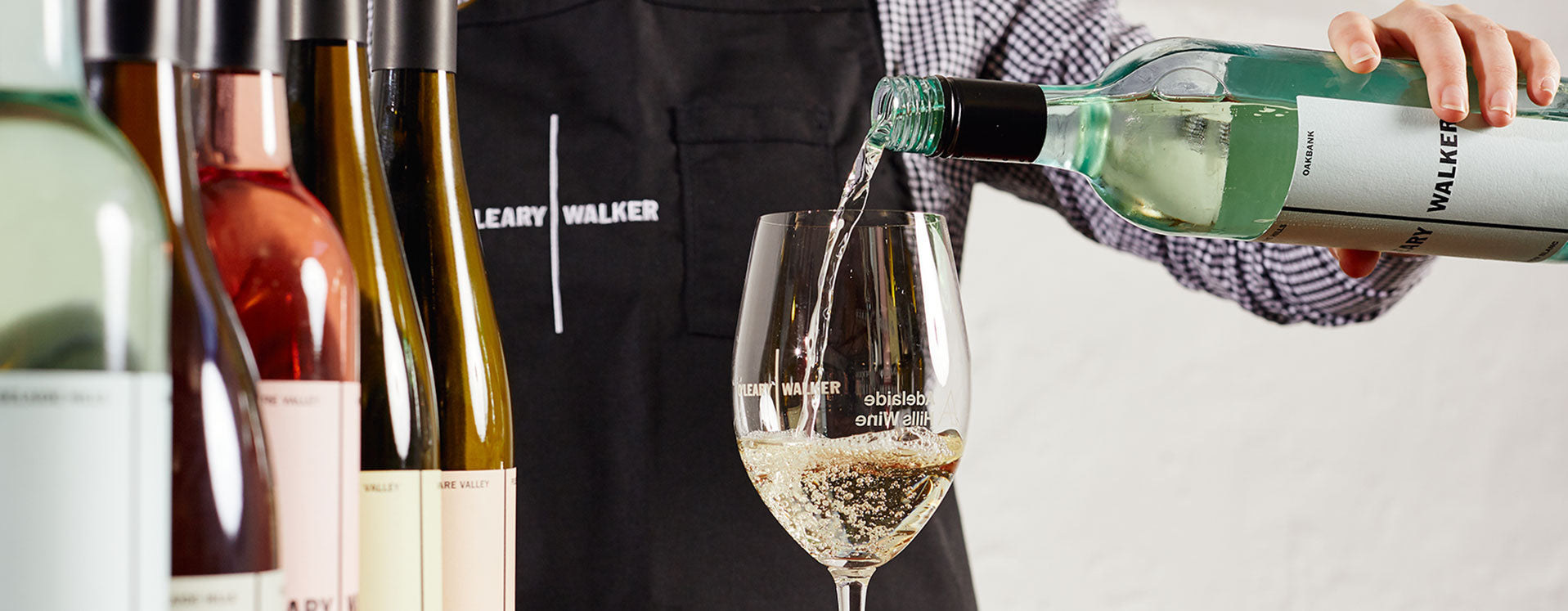 Close up of an O'Leary Walker staff member in a checkered shirt and black apron, pouring a glass of Sauvignon Blanc. Five other bottles of wine are lined up next to the glass.