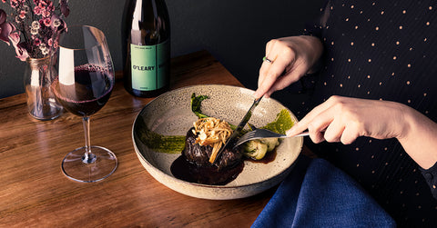 Hands with knife and fork positioned over steak and enoki mushrooms, glass of shiraz to the side
