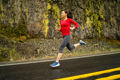 A woman running on road wearing Topo Phantom Running Shoes
