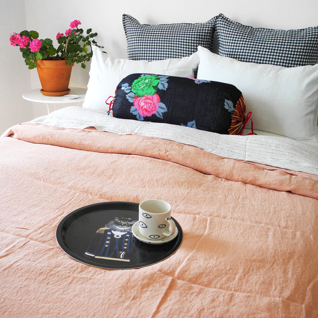 Round designer tray in Scandinavian tray style with a black background and cat portrait on a linen duvet with mug - Collyer's Mansion