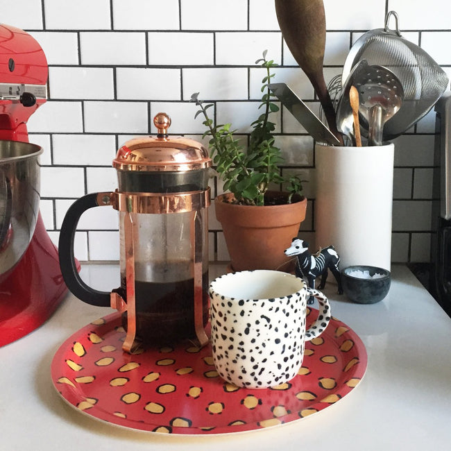 Round designer tray in coral orange animal print serving coffee with a speckled mug and french press - Collyer's Mansion