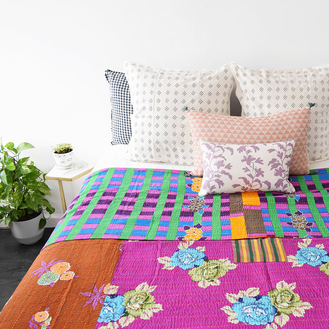 Colorful lilac vine pillow mixed with other pillows for colorful home decor and a vibrant bedding look - Collyer's Mansion