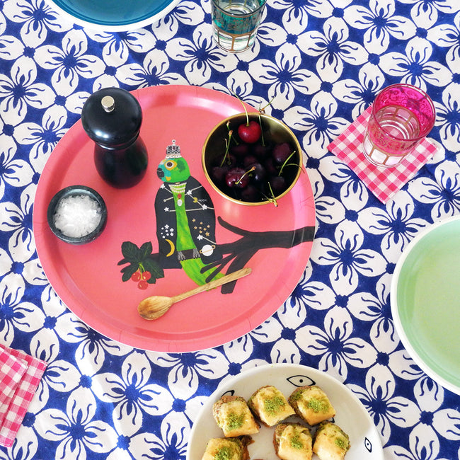 Round designer tray in Scandinavian tray style with a pink background and parrot portrait on dining table with food - Collyer's Mansion