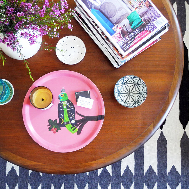 Round designer tray in Scandinavian tray style with a pink background and parrot portrait on coffee table with candle - Collyer's Mansion
